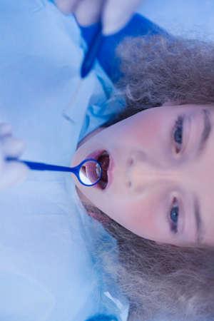 angled: Pediatric dentist using dental explorer and angled mirror at the dental clinic