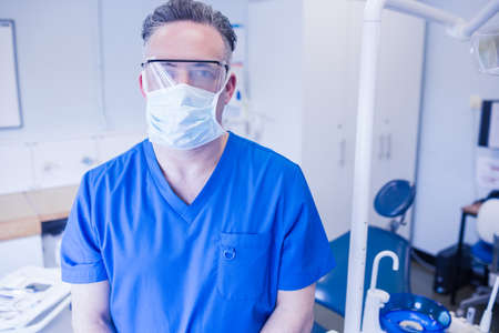 surgical mask: Dentist wearing surgical mask and safety glasses at dental clinic