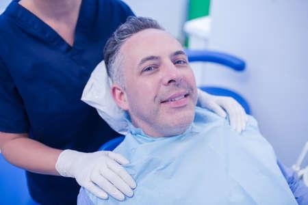 examined: Man having his teeth examined by a dentist