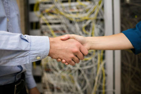 technician: Technicians shaking hands in server room at the data centre