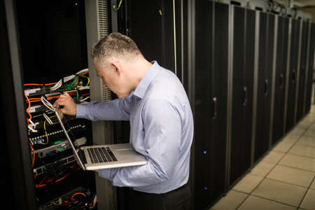 data storage: Technician looking at open server locker at the data centre