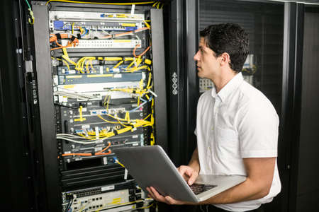 server hardware: Technician using laptop to analyse server at the data centre