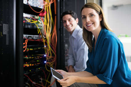 Team of technicians working together on servers at the data centre