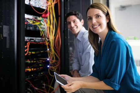 Team von Technikern, die gemeinsam an Servern im Rechenzentrum LANG_EVOIMAGES