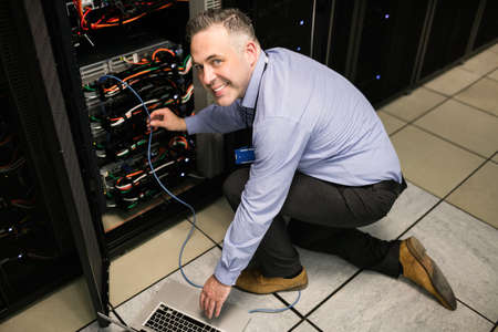 technician: Technician using laptop to analyse server at the data centre