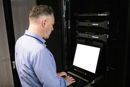 server room: Technician using laptop in server room at the data centre