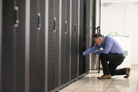 equipos: Técnico de pie en el pasillo del servidor en el centro de datos
