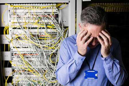 computer center: Stressed technician looking at open server locker at the data centre LANG_EVOIMAGES