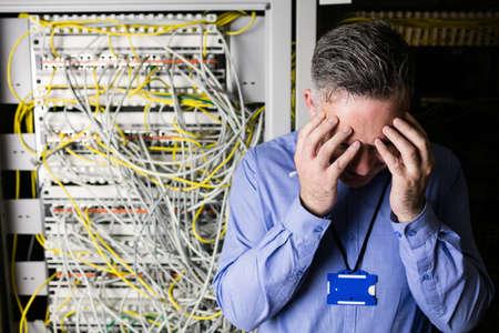 centro de computo: T�cnico tensionado mirando casillero servidor abierto en el centro de datos