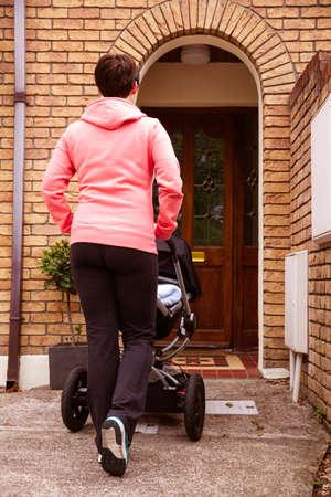 pram: Mother pushing pram going at home LANG_EVOIMAGES