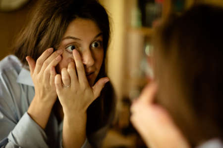 putting in: Young woman putting in contact lens at mirror
