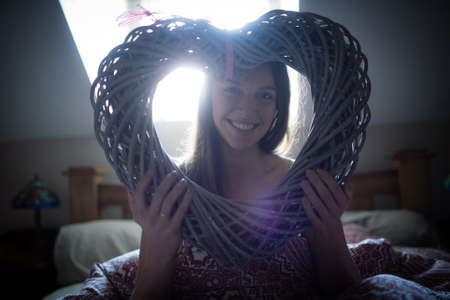 bed frame: Smiling young girl sitting on bed holding frame heart