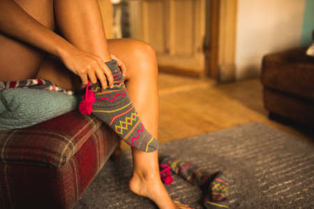 putting on: Cropped image of woman putting on warm socks at home