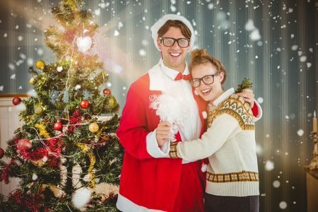 fake christmas tree: Geeky hipster in santa costume hugging his girlfriend against home at christmas time