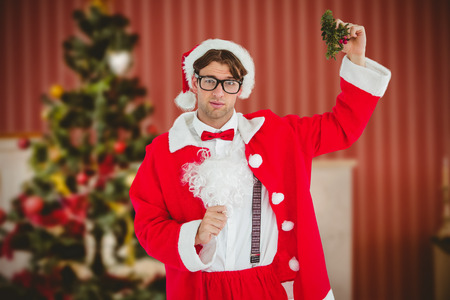 fake christmas tree: Geeky hipster in santa costume holding mistletoe   against home at christmas time Stock Photo