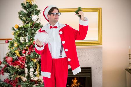 fake christmas tree: Geeky hipster in santa costume looking at mistletoe  against christmas tree in living room