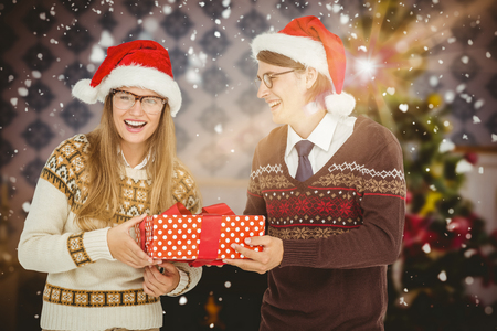 christmas time: Geeky hipster couple holding present  against home at christmas time Stock Photo