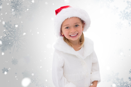 wearing santa hat: Cute little girl wearing santa hat  against snowflake pattern