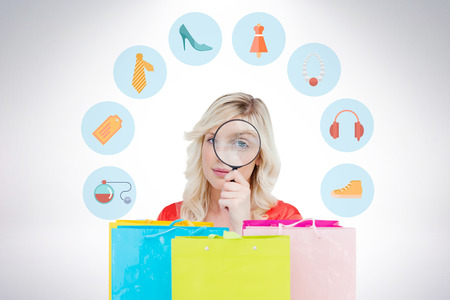 jewlery: Fair-haired woman looking through a magnifying glass against gift bags
