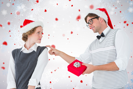 cheesy grin: Geeky hipster offering present to his girlfriend against snowflake pattern