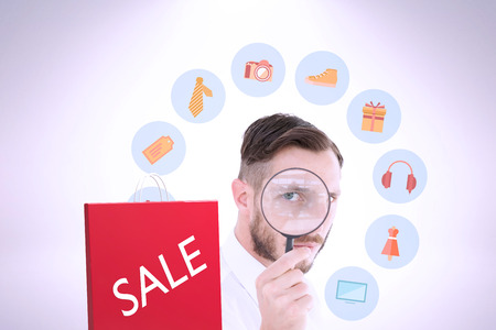 western script: Geeky businessman looking through magnifying glass against red shopping bag on white background