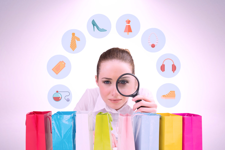 jewlery: Businesswoman typing and looking through magnifying glass against gift bag Stock Photo