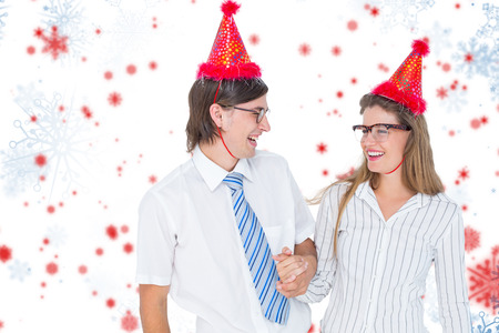 cheesy grin: Happy geeky hipster couple with party hat  against snowflake pattern