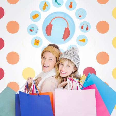 jewlery: Beautiful women holding shopping bags looking at camera  against colorful polka dot pattern Stock Photo