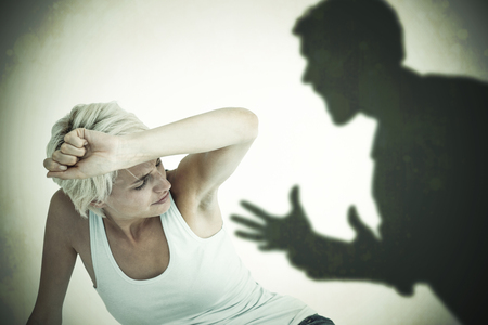 cowering: Depressed woman on the floor  against silhouette of shouting man