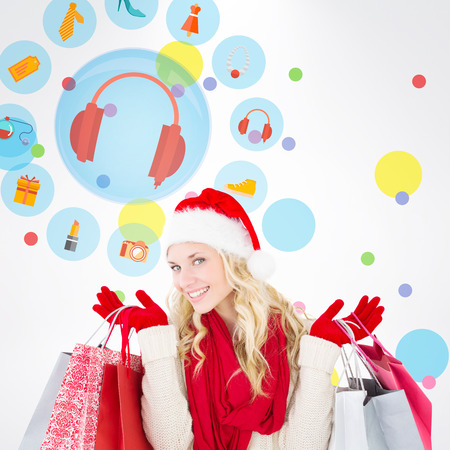 christmas perfume: Happy festive blonde with shopping bags against dot pattern