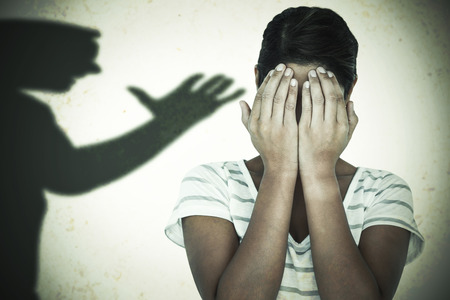 covering the face: Close-up of upset woman covering face with hands against silhouette of man with raised hand Stock Photo