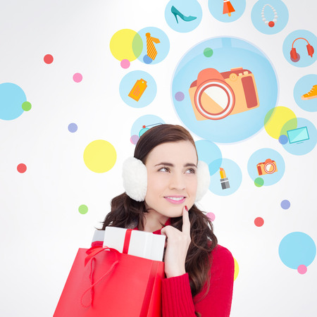 ear muffs: Brunette with ear muffs holding shopping bag full of gifts against dot pattern Stock Photo