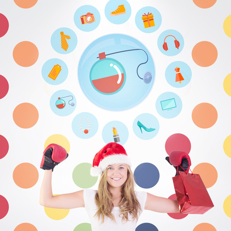 christmas perfume: Festive blonde with boxing gloves and shopping bag against colorful polka dot pattern Stock Photo
