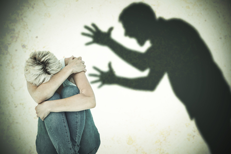 cowering: Depressed woman hiding her head  against silhouette of shouting man