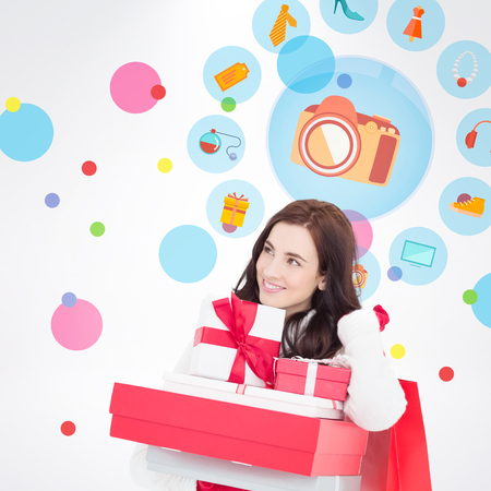 jewlery: Happy brunette holding christmas gifts and shopping bags against dot pattern