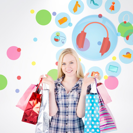 jewlery: Pretty young blonde holding shopping bags against dot pattern Stock Photo