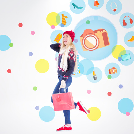 jewlery: Festive blonde holding shopping bags against dot pattern Stock Photo
