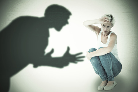 cowering: Crouching sad woman holding her hand against silhouette of shouting man