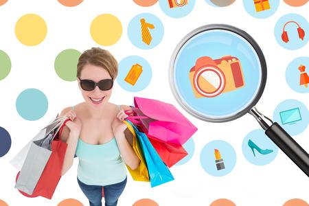polka dot pattern: Woman holding shopping bags wearing sunglasses  against colorful polka dot pattern