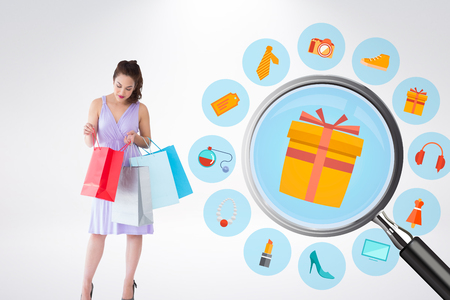 woman looking down: Stylish brunette in purpul dress opening shopping bag against online shopping wheel