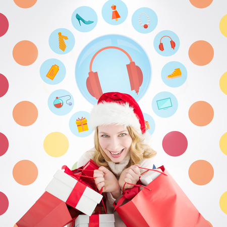 christmas perfume: Girl in winter fashion holding presents and shopping bags against colorful polka dot pattern