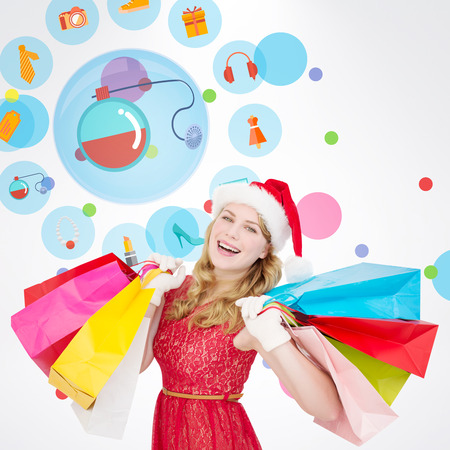 christmas perfume: Excited blonde in santa hat holding shopping bags against dot pattern