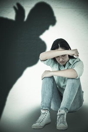 Traurig, Frau sitzt auf dem Boden und verbarg ihr Gesicht gegen die Silhouette der Mann mit erhobener Hand Standard-Bild