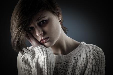 lonesomeness: Pretty brunette feeling sad  against blue background with vignette Stock Photo