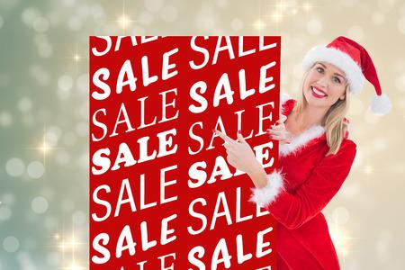 pere noel sexy: Festive blond montrant carte blanche contre la conception lumi�re chatoyante sur l'argent