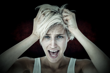 apprehensive: Stressed woman screaming and holding her head  against dark background