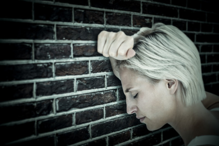 unhappiness: Sad blonde woman with her head on wall  against red brick wall