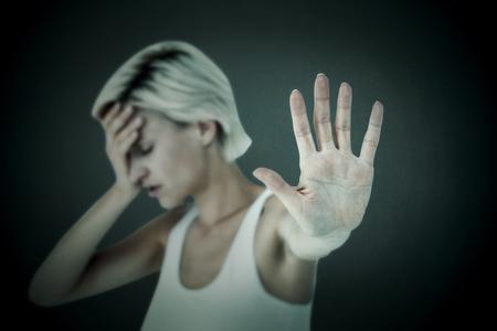 desolaci�n: Rubia triste que sostiene su mano contra el fondo gris