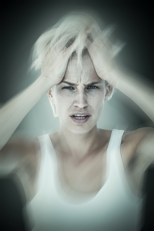 Sad blonde woman with head pain holding her head  against grey vignette Stock Photo