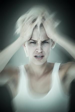 desolaci�n: Sad blonde woman with head pain holding her head  against grey vignette Foto de archivo